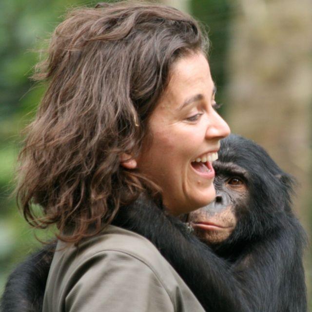 Isabel Behncke riendo con un simio en brazos.