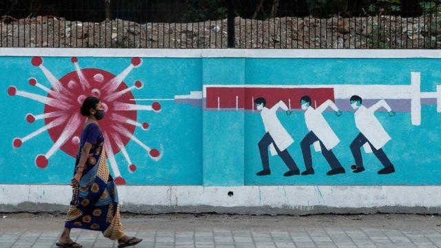 一个戴着口罩的女人走过抗击新冠病毒的宣传画