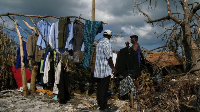 Personas afectadas colgando ropa en ramas de árboles