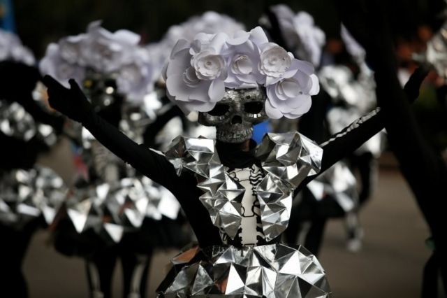 A participant wearing a skull mask performs during the annual Day of the Dead parade in Mexico City