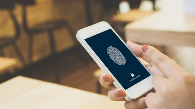 Finger over thumbprint scanner on phone