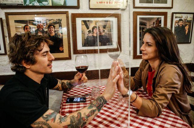Los dueños de un restaurante en Italia prueban los separadores de plexiglass que planean adoptar para poder reabrir su negocio de forma segura.