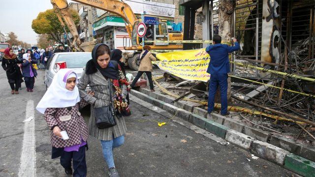 Женщина и девочки идут по улице на фоне сгоревшего банка
