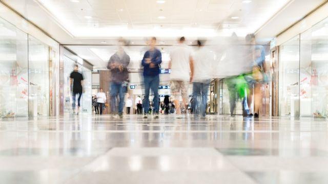 Vultos de pessoas caminhando em corredor de shopping