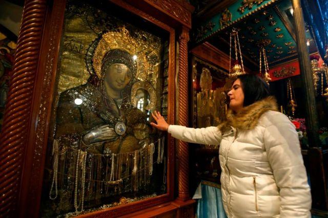 Женщина перед иконой в храме Рожедества Христова в Вифлееме