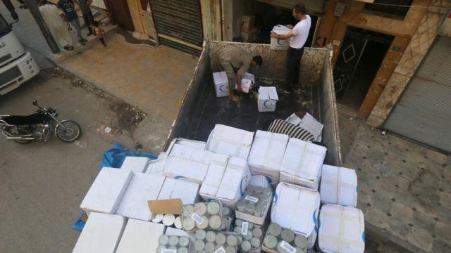 Trabalhadores descarregam ajuda em Aleppo