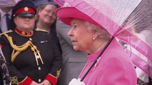 Queen wearing pink with matching umbrella at Buckingham Palace garden party