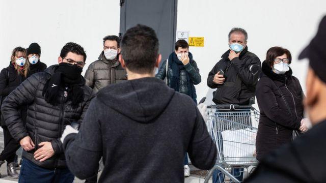 اهالی شهرک کاسالپوسترلنیو در شمال غربی میلان در صف سوپرمارکت