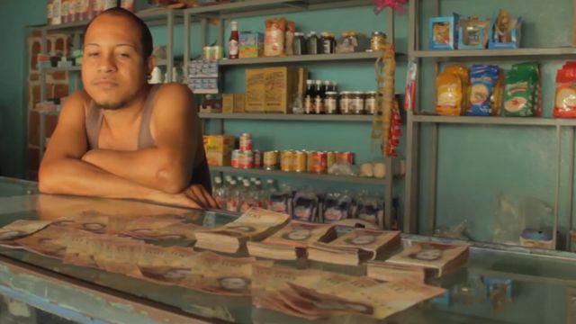 Álex y billetes de bolívares sobre el mostrador.