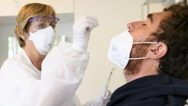 Enfermeira coleta material do nariz de um homem