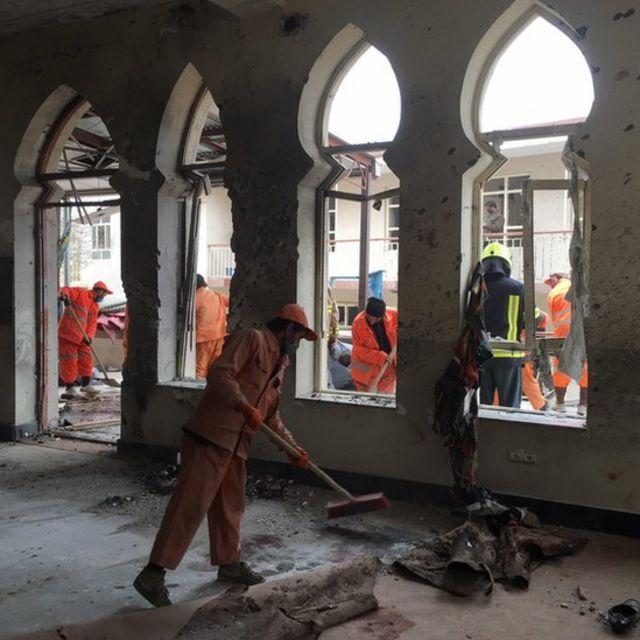 عمال أفغان ينظفون موقع الانفجار في المسجد