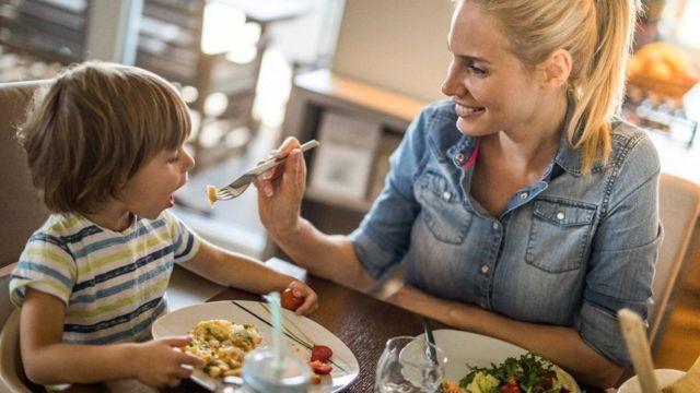 Mujer dando de comer a un niño.