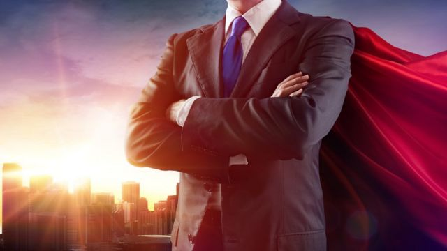 Мужчина в деловом костюме и плаще супермена на фоне небоскребов