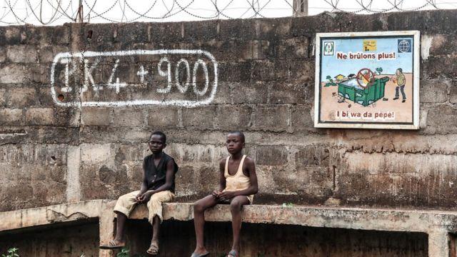 Deux jeunes garçons assis devant devant un mur au sud de la ville de Bangui.