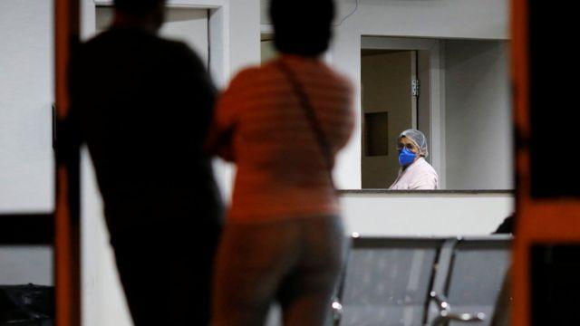 Enfermeira com máscara e vulto de duas pessoas dentro de sala de hospital em Brasília