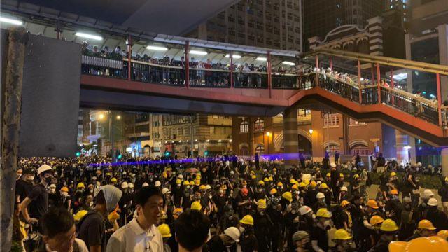 上环冲突现场,示威者有数百人。 其中一些人开始向警察投掷头盔和雨伞。