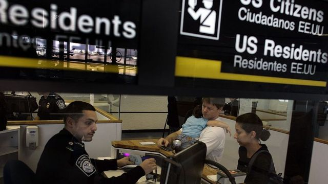 Oficial de imigração checa passaporte de casal
