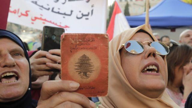 протесты в ливане, женщина в хиджабе держит паспорт