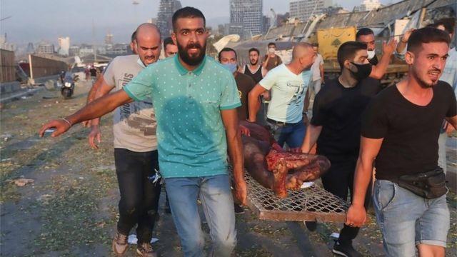 varios hombres trasladan a un herido tras la explosión en BEirut.