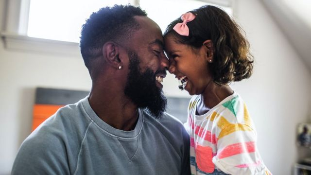 Father and daughter laughing in the bedroom