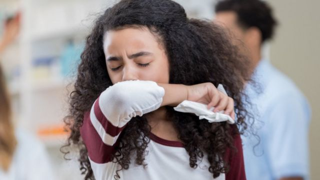 Adolescente estornudando en la parte interna del codo.
