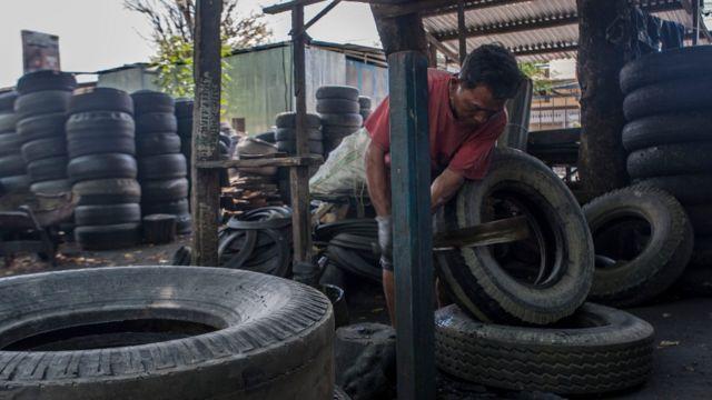 Hombre en un taller trabajando con neumáticos usados
