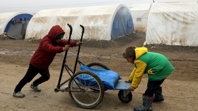An internally displaced Syrian boy pushes a cart at a camp in the Northern Aleppo countryside, Syria December 19, 2020
