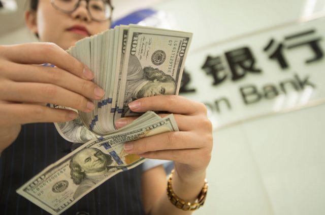 Una cajera de un banco chino contando dólares