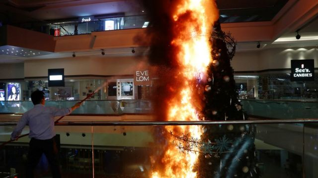 A Christmas tree inside a shopping mall on fire