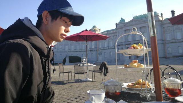 Morimoto tomando café em uma praça