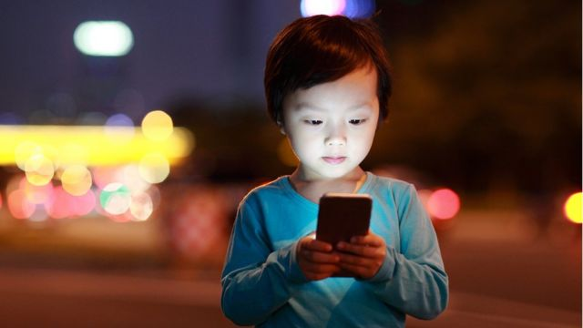 Niña asiática usando celular