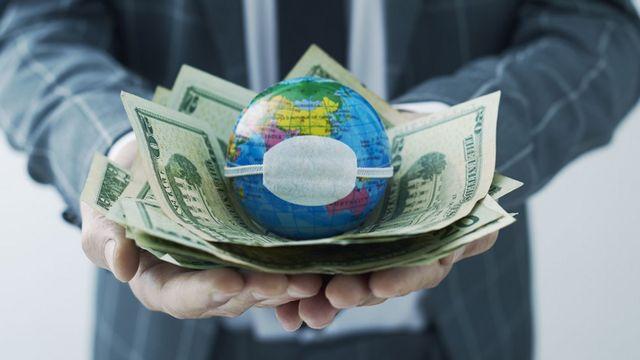 A world globe with a mask on dollar bills