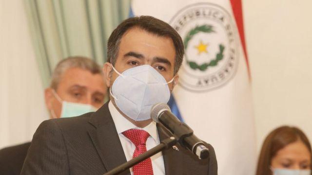 Ministro fala no microfone, de máscara