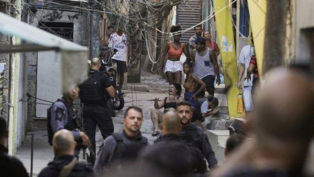 Em rua da favela cheia de moradores e policiais, mulheres choram em escada