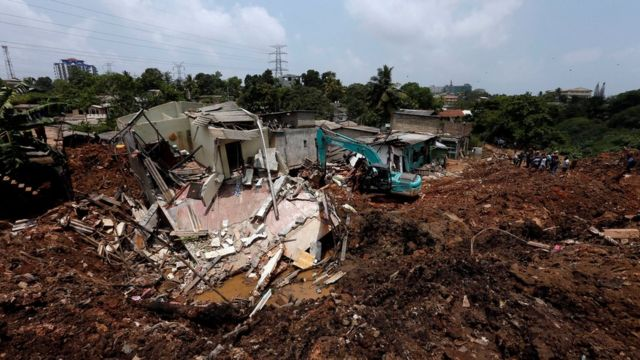 A bako machine works near damaged houses during a rescue mission after a garbage dump collapsed and buried dozens of houses in Colombo