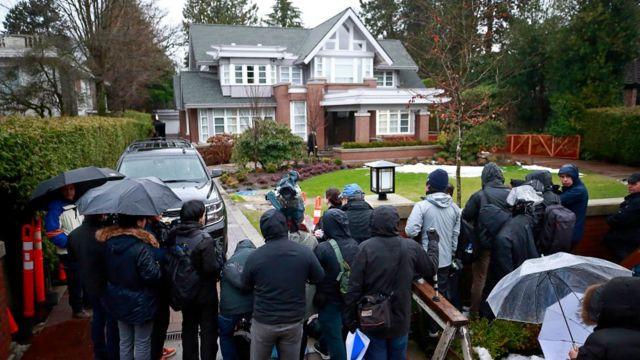 Los medios de comunicación se paran frente a la casa de Meng Wanzhou.