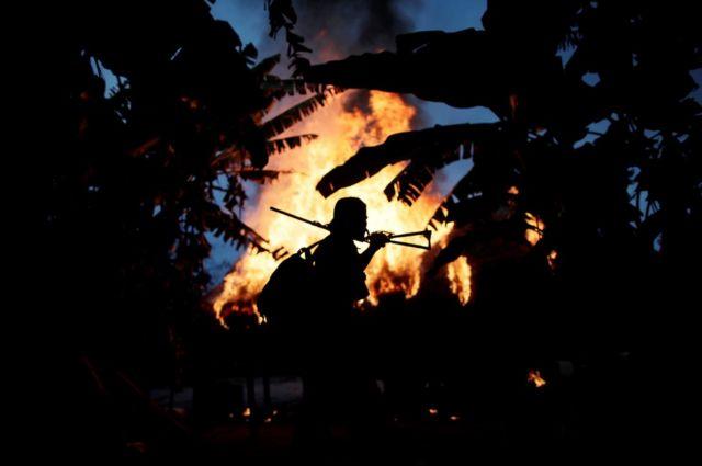 Представитель бразильского народа гуажажара возле горящего лагеря нелегальных лесорубов