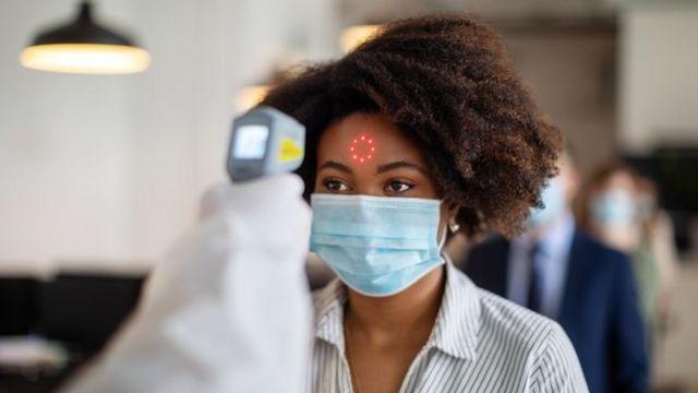 Uma mulher usando uma máscara cirúrgica mede a febre usando um leitor em sua testa