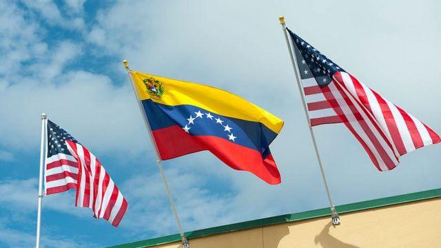 Bandera de Venezuela entre dos banderas de Estados Unidos.