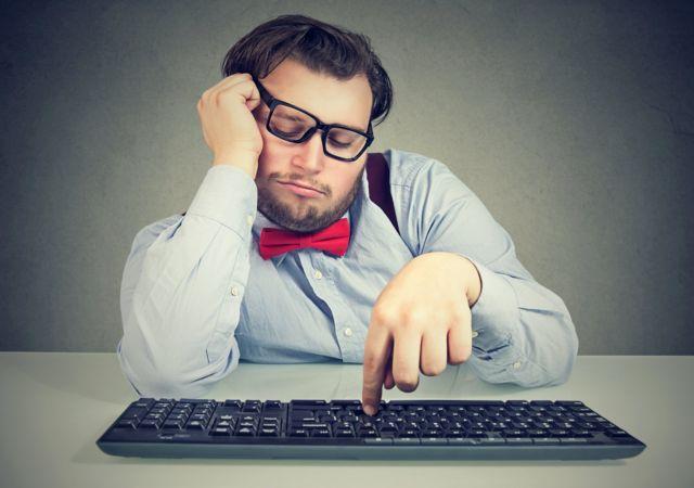 Hombre con teclado de ordenador siendo perezoso.
