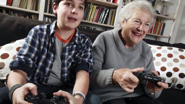бабушка с внуком играют на игровой приставке