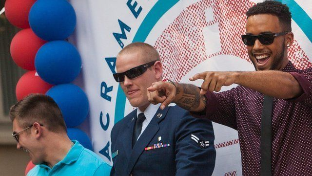 Alek Skarlatos, Spencer Stone, and Anthony Sadler, who helped thwart an attack on a French train last August, wave to the crowd during a parade honouring them in Sacramento, California.
