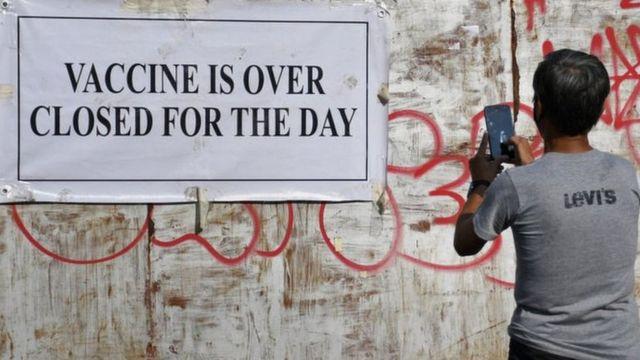 এক ব্যক্তি মুম্বাইতে ইউনেস্কো ব্যাকসিনেশন সেন্টারের বাইরে একটি নোটিশ বোর্ডের ছবি তুলছেন যেখানে লেখা 'ভ্যাকসিন নেই- আজকের মত বন্ধ'