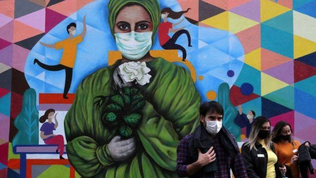 Três pedestres com máscaras passam em frente a grafite que retrata mulher profissional de saúde