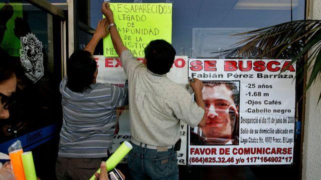 Personas colocan letreros de desaparecidos.