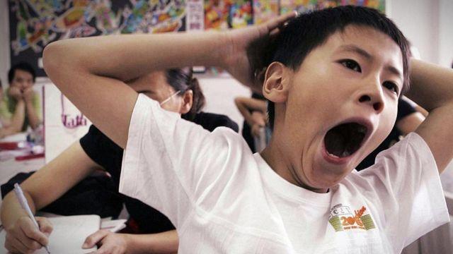 Menino boceja em sala de aula