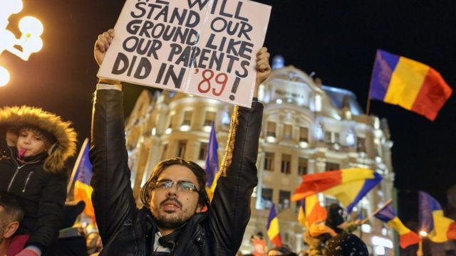 Un hombre con un cartel durante una protesta en Rumania