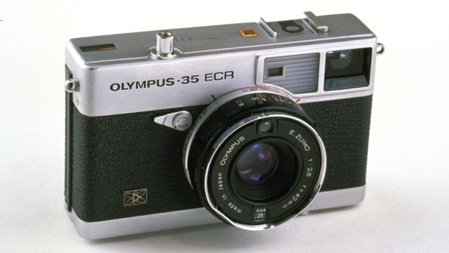 """An Olympus-35 ECR rangeinfer-style camera with a short """"pancake"""" lens is seen here against a white background"""