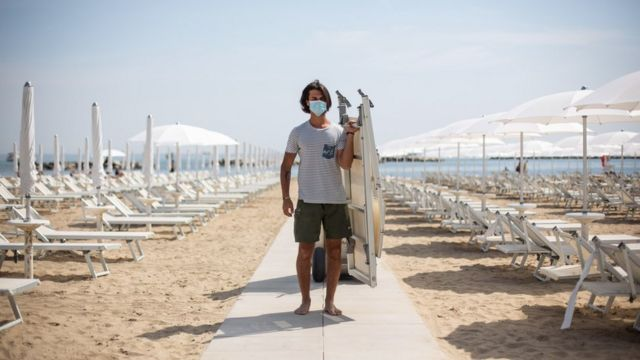 A man wearing a mask laying out deck chairs in Italy