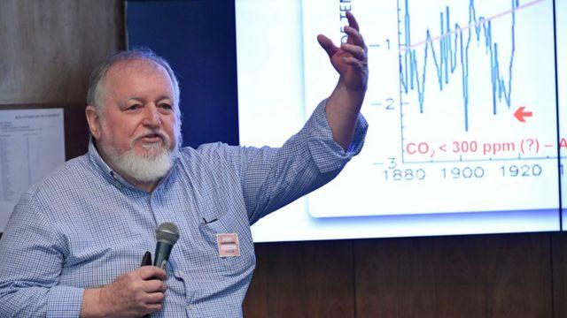 Luiz Carlos Molion fala no microfone com gráfico ao fundo